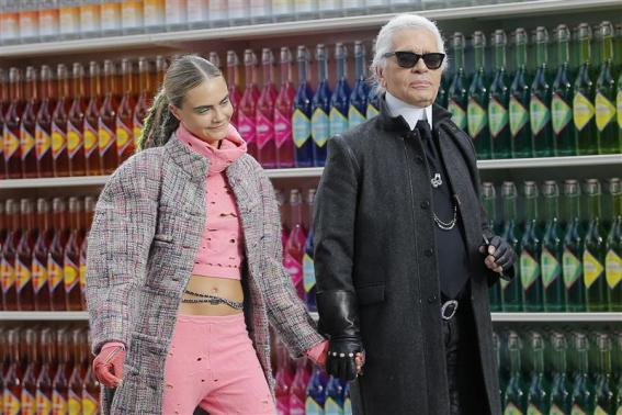 """German designer Lagerfeld and model Delevingne appear at the end of his Fall/Winter 2014-2015 women's ready-to-wear collection show for French fashion house Chanel at the Grand Palais transformed into a """"Chanel Shopping Center"""" during Paris Fashion Week"""